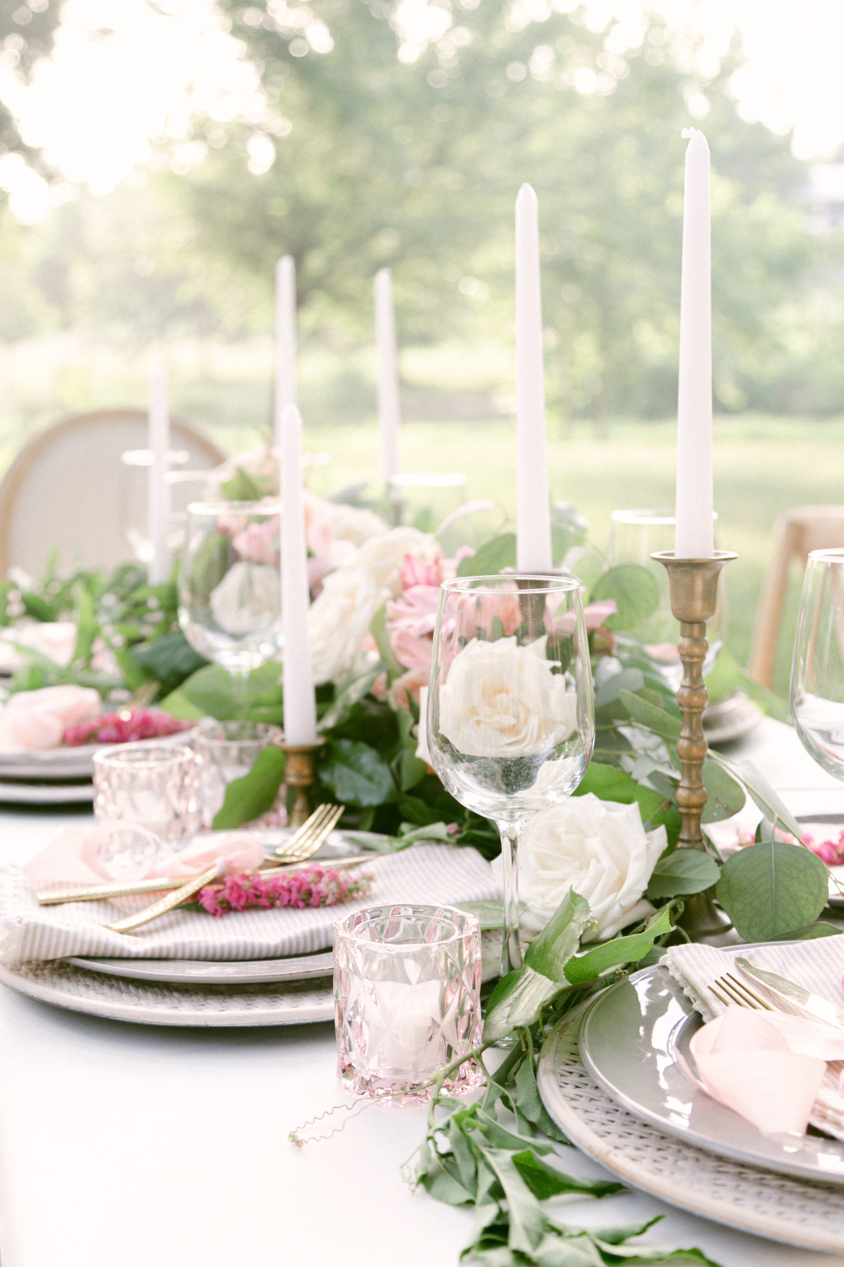 a close of of the outside table, the table is set with flowers and candle sticks