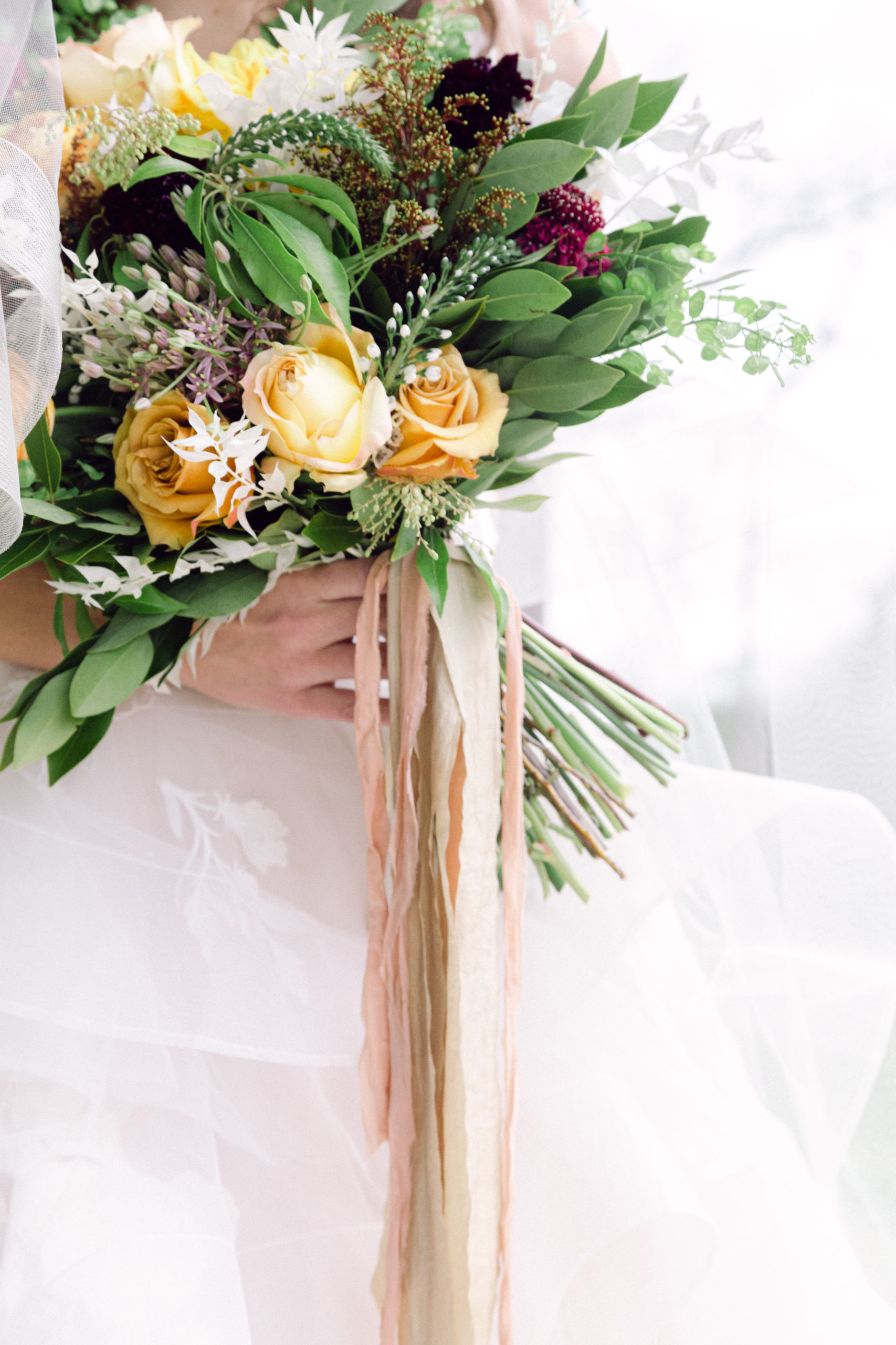 a bouquet of greens and yellows and whites is held by the bride at an angle