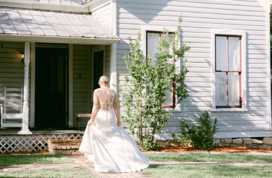 a bride walks back to the bridal suite. This photos is being used as a feature image for the A Green Garden Wedding